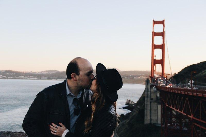 Man och kvinna kysser vid bro. Foto: Unsplash