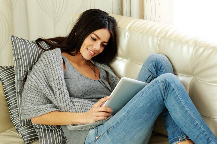 Happy young woman resting on a sofa with tablet computer at home
