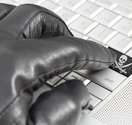 Hacking concept with hand wearing black leather glove pressing enter key with flag overlaid