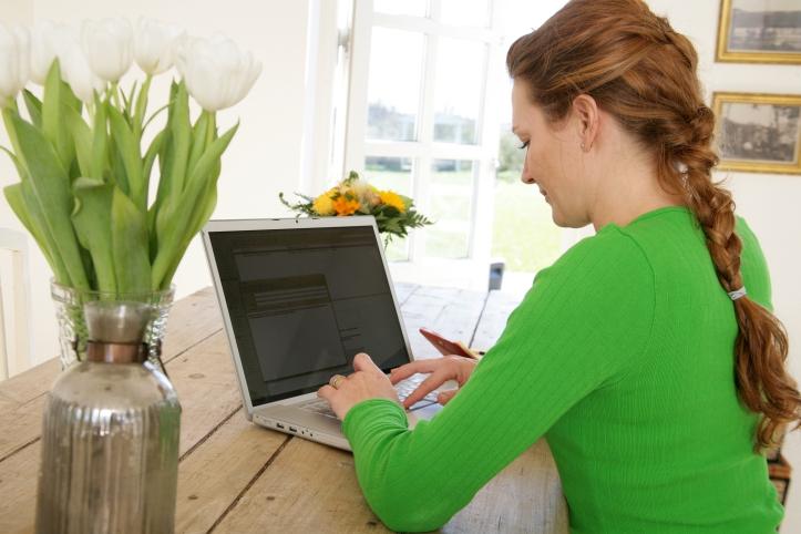 Ung kvinna vid dator söker bostad.